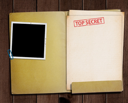 folder with TOP SECRET stamped across the front page and a blank photograph Foto de archivo