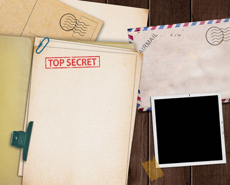 folder with TOP SECRET stamped across the front page and a blank photograph photo