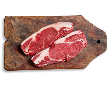 argentinean: Argentinean bife de chorizo raw meat on wooden table. Clipping path excludes shadow.