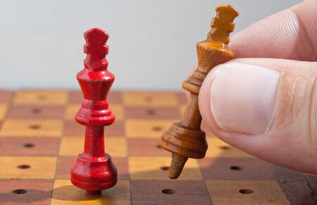 jugando ajedrez: Mano con el juego de los reyes de ajedrez de madera.