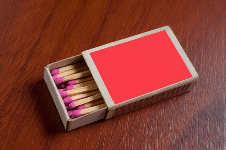 match box: Red Match box on wooden table.