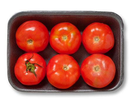 Red tomatoes in a plastick pack. Isolated, white background, clipping path excludes the shadow. photo
