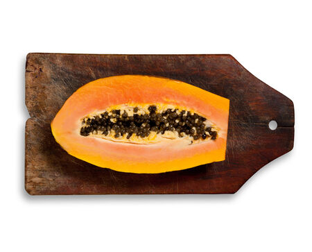 excludes: Sliced fresh papaya on wooden table. White background, clipping path excludes the shadow. Stock Photo