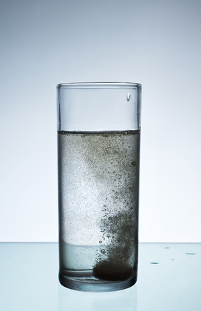 effervescent: Glass with efervescent tablet in water with bubbles. Stock Photo