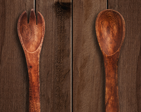kitchen tool: Wooden spoon and fork on table.