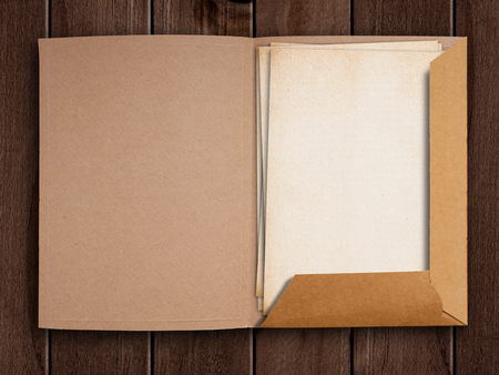 folder with documents: Old open folder on wooden table. Stock Photo
