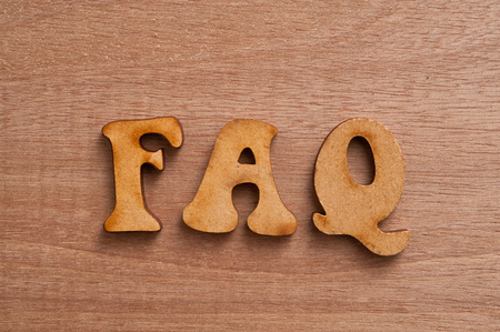 faqs: FAQs  Text with wooden background. Stock Photo