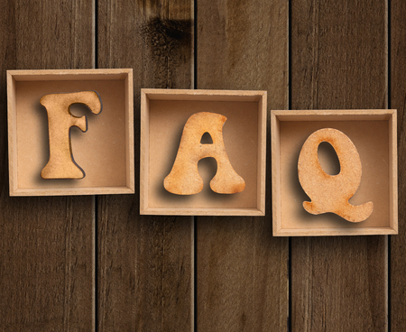 IMAGE: FAQs  Text with wooden background. Stock Photo