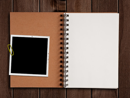 stationery: White paper notebook with photograph on wooden table. Stock Photo