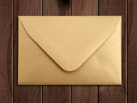 Golden envelope over wooden table.