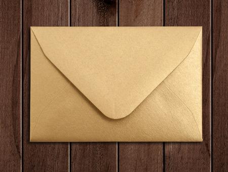 envelope: Golden envelope over wooden table.
