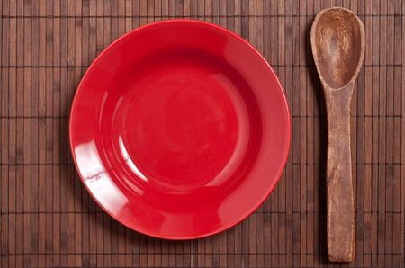 red plate and wooden spoon on table.