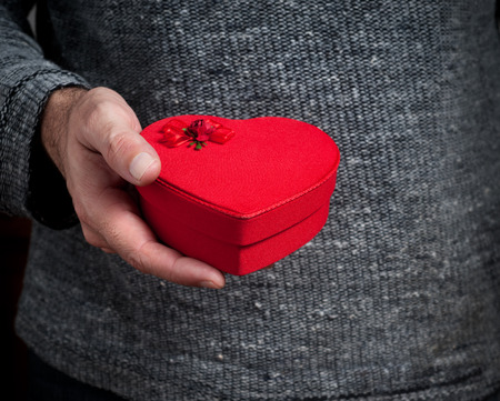 Man holding red heart shaped box