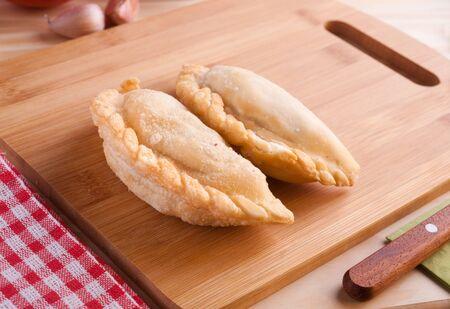 argentine: Argentine empanadas on wooden table. Stock Photo