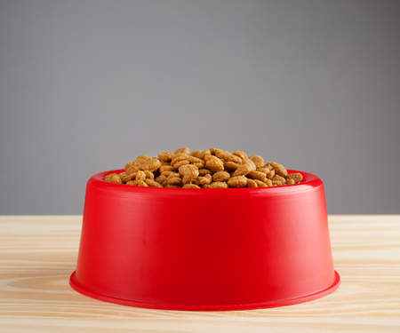 Cat food on red plastic bowl.
