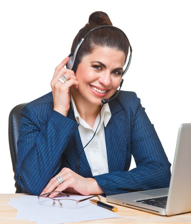woman business suit: Beautiful smiling  woman using a computer and a headset, looking at camera. Stock Photo
