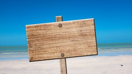 blank rustic wooden sign on the beach