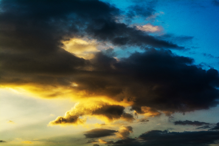 Beautiful big dark storm clouds illuminated by the sun in the blue sky