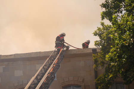 Firemen at the roof during fire photo