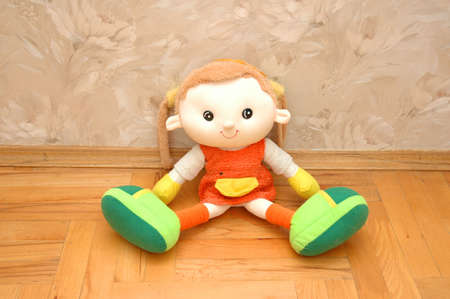 Doll sitting on the wooden floor photo