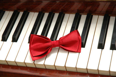 Red bow-tie on piano keys photo