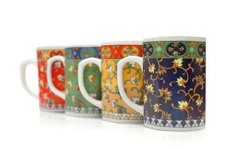 Four colourful mugs isolated on white photo