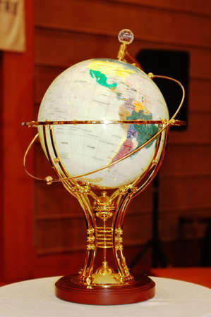 Globe with golden frame on the table photo