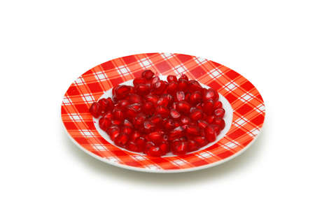 Plate full of red pomegranate seeds isolated on white photo