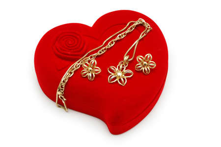 Golden earrings and chain on red heart-shaped box photo