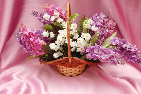 Basket of lilac flowers on lilac background photo