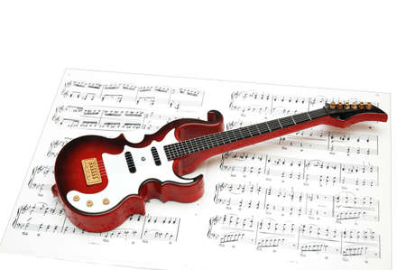 Rock guitar over the sheet of printed music