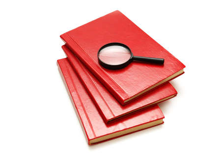 Three books and magnifying glass isolated on white photo