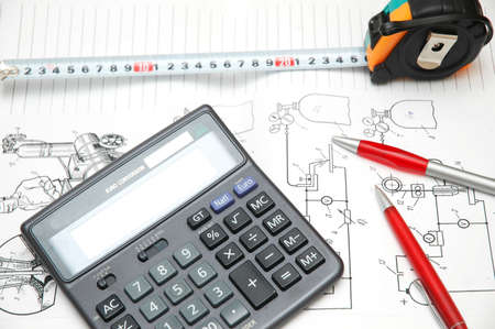 Design drawings, calculator, pens and measuring tape photo