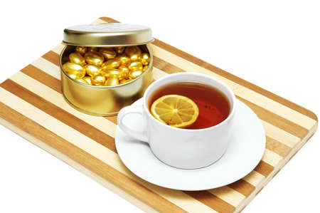 Cup of tea with lemon and chocolates isolated on white Stock Photo - 730340