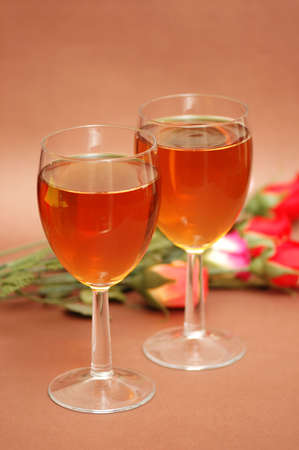 Two wine glasses and flowers at the background photo