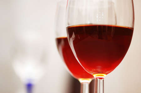 Two wine glasses against the red background