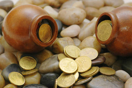 Two pots with coins on the pebbles photo