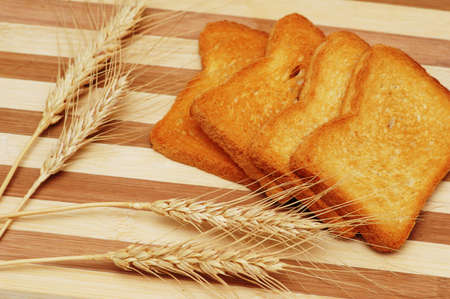 Four toast pieces and wheat ears on wooden board photo