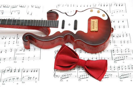 Guitar and bow tie over the sheet of printed music Stock Photo - 778890