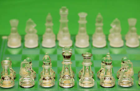 Glass chess figures against green background photo