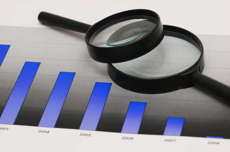 Studying business opportunities - magnifying glasses over the bar charts Stock Photo