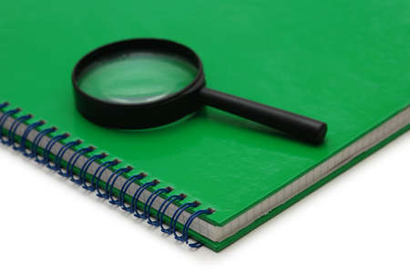 Magnifying glass over the green notebook isolated on white Stock Photo - 778054