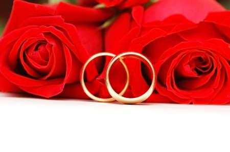 Two wedding rings and red  roses isolated on white Stock Photo - 803568