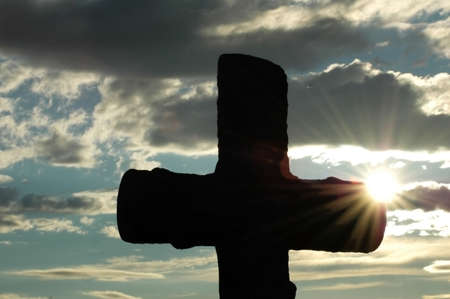 Silhouette of a cross  against evening sun