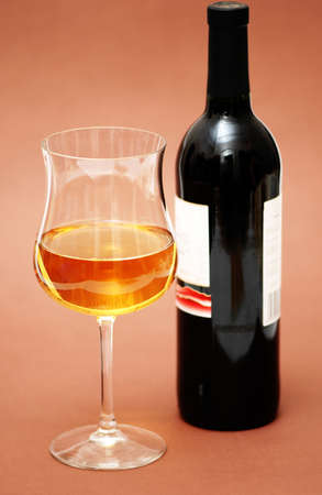 biege: Glass of wine and a bottle on biege  background Stock Photo