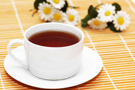 Cup of black tea and camomiles  at the background photo