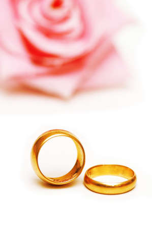 Two golden wedding  rings and a pink rose photo