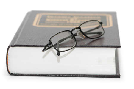 Reading glasses over the  book isolated on white photo