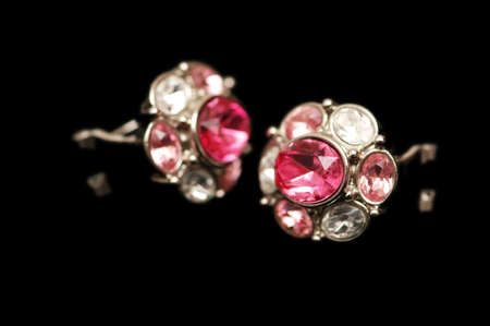 Pair of earrings isolated on  the black photo