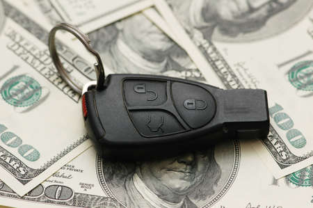 Car remote over  the hundred dollar banknotes photo